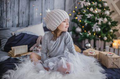 Niña juega delante arbol de navidad