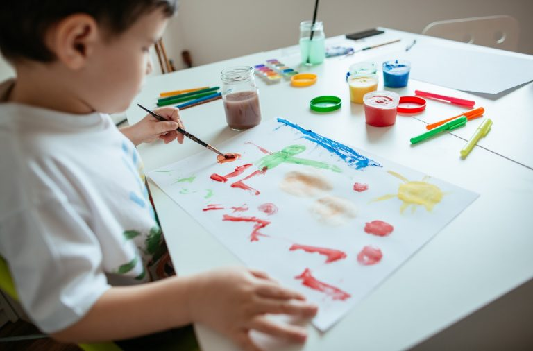 Left handed child painting picture.