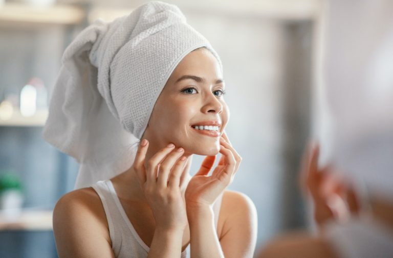 Millennial girl looking at her face with silky skin after bath in mirror at home