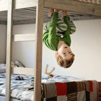 A little boy hangs like a monkey from a bunk bed..