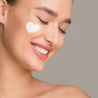 Anti wrinkle cream. Woman with cream in heart shape