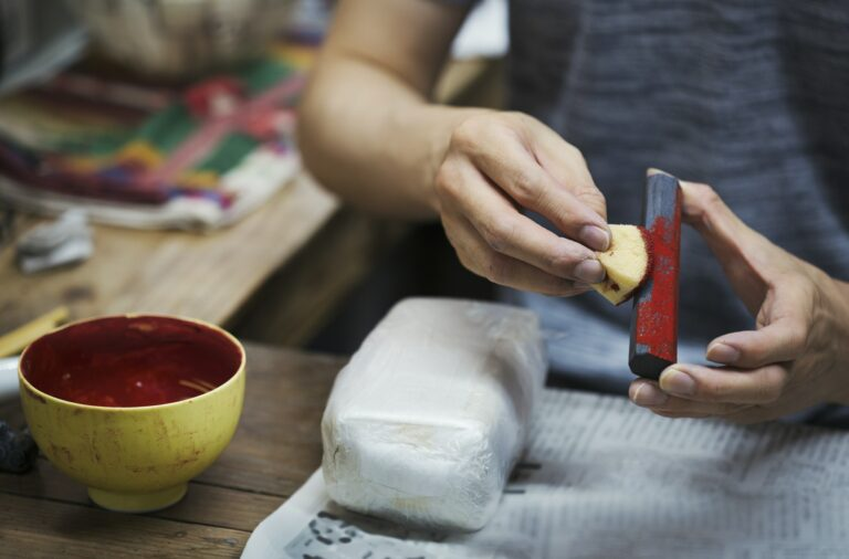 Close up of woman working in a Japanese porcelain workshop, holding red paint stick and sponge.