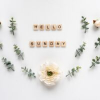 Hello Sunday words on white marble background