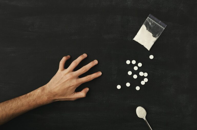 Man's hand reaching for drugs on dark table