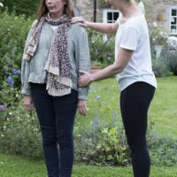 Therapist focussing on the standing posture of a client in a garden.