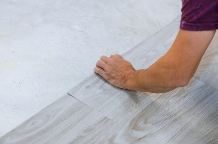 Work on laying worker installing new vinyl tile laminate wood texture floor.