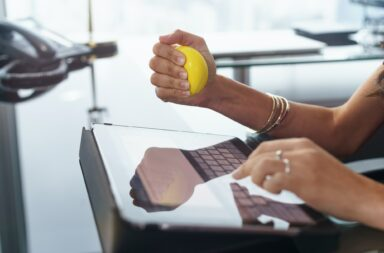Stressed Office Worker With Anti Stress Ball Types Email
