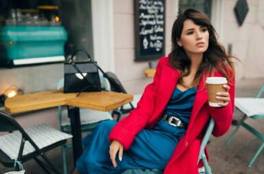 stylish woman in red coat sitting in cafe